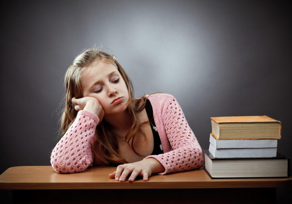 Skoletrøtt jente med bokstabel