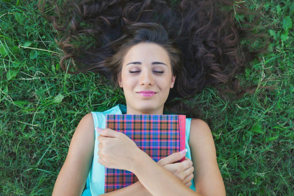 jente med bok, ligger i gresset