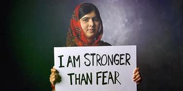 Malala holding a poster:I am stronger than fear