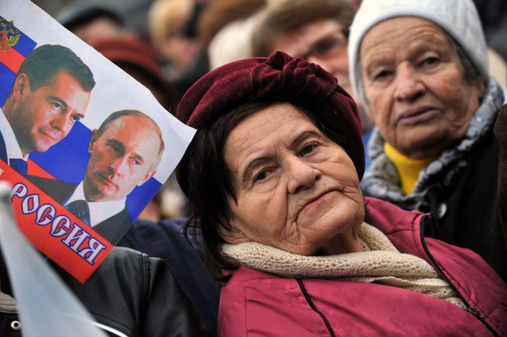 An elderly woman stands next to a flag depicting Russian President Vladimir