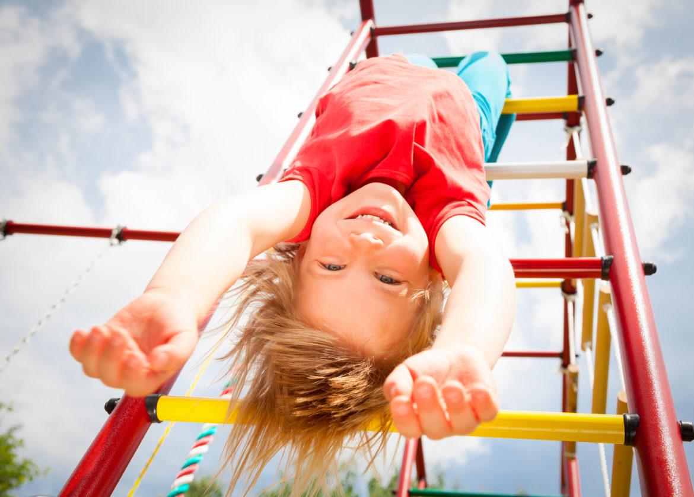Smilende jente henger i klatrestativ