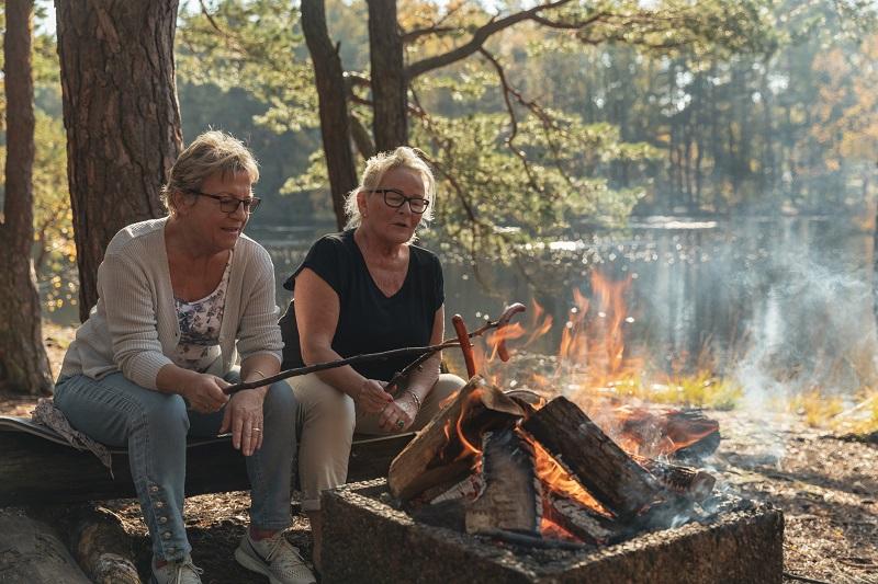 To godt voksne kvinner griller pølser på et bål i skogen, rett ved et vann.