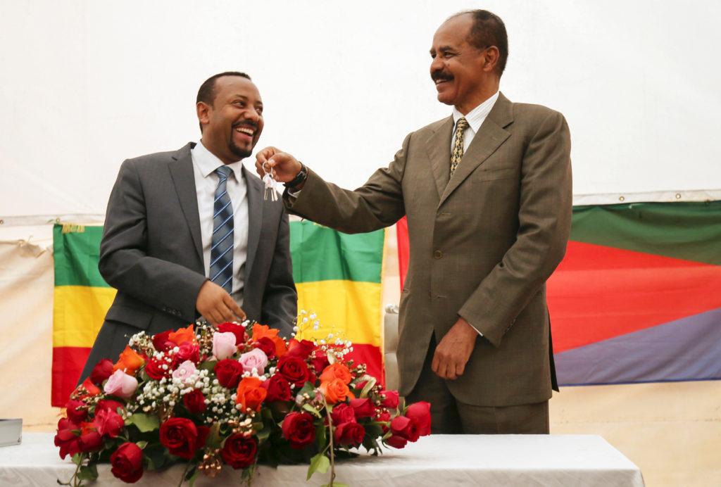 Abiy Ahmed til venstre og Isaias Afwerki til høyre. Begge smiler. Afwerki holder opp et nøkkelknippe.