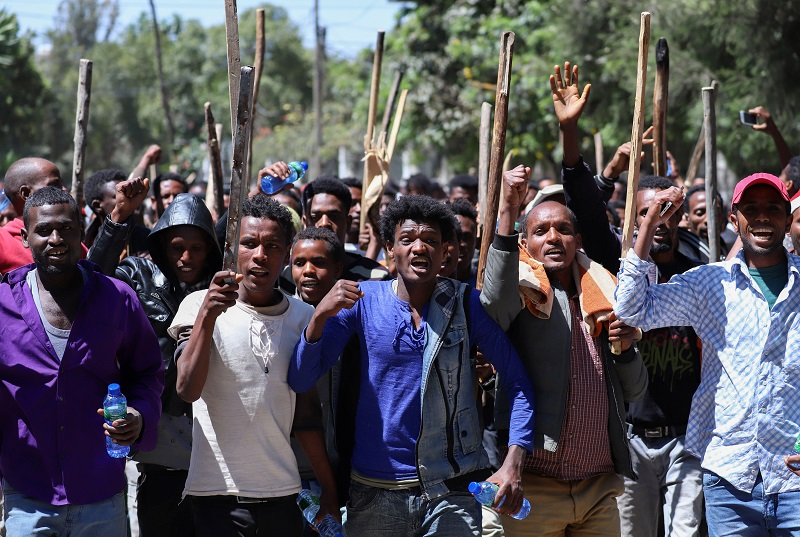En demonstrasjon med mange menn som roper og vifter truende med stokker.