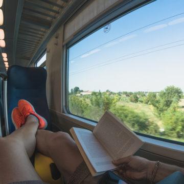 Vi ser beina til en person som sitter og ser ut av vinduet på et tog, med en bok i fanget.