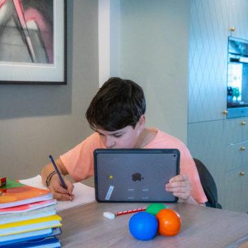 Gutt i barneskolealder gjør skoleoppgaver ved kjøkkenbordet. Han holder et nettbrett og skriver for hånd ved siden av. Skolebøker og noen fargerike leker på bordet.