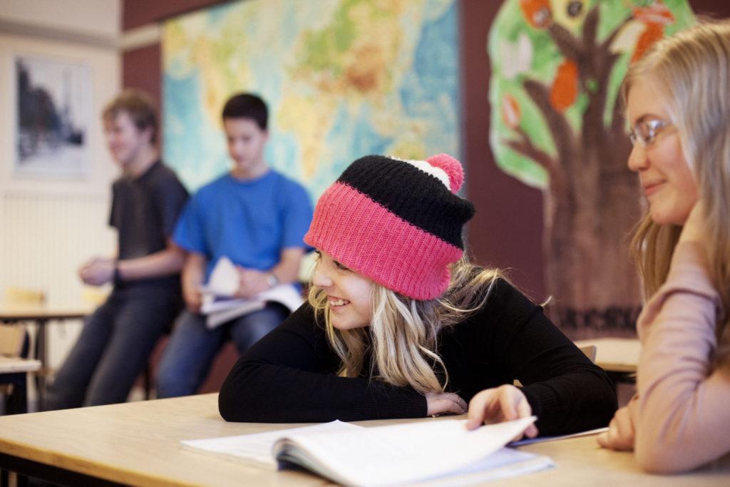 To tenåringsjenter og to gutter i bakgrunnen i et klasserom. Den ene jenta har en sort og rosa lue på seg.