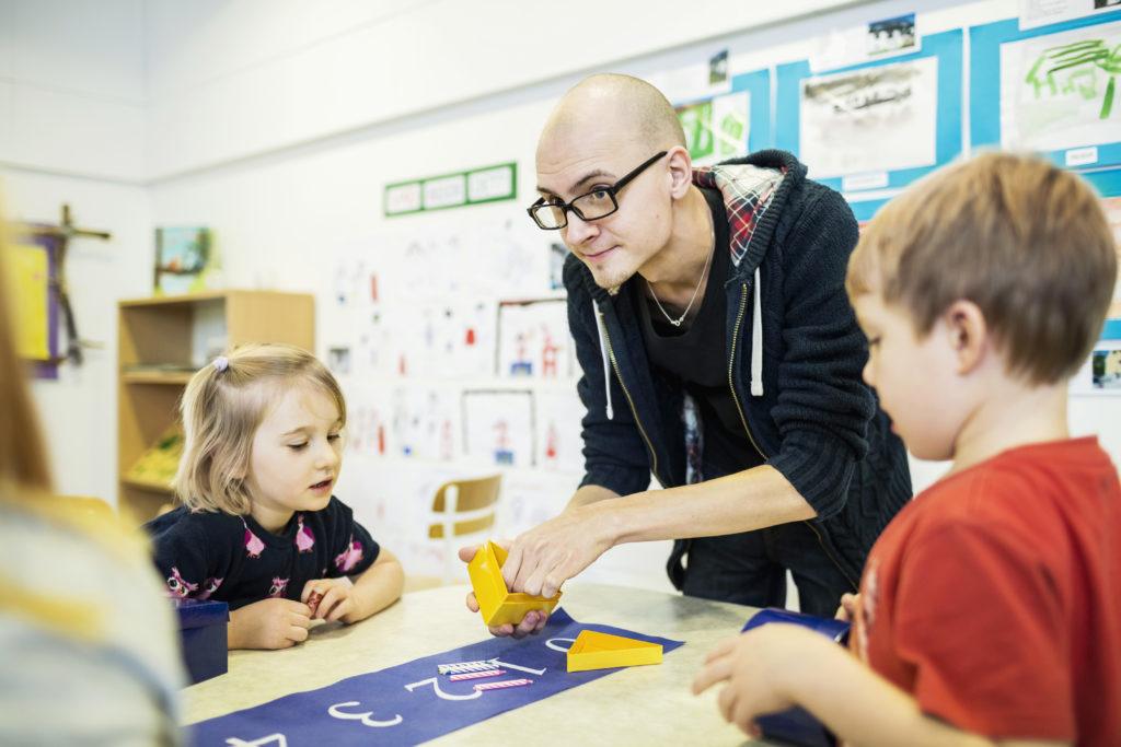 Mannlig lærer hjelper to barneskoleelever med oppgaver om tall
