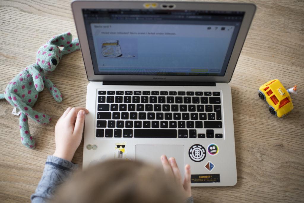 Et lite barn gjør oppgaver på PC. En bamse og lekebil på hver sin side av skjermen.