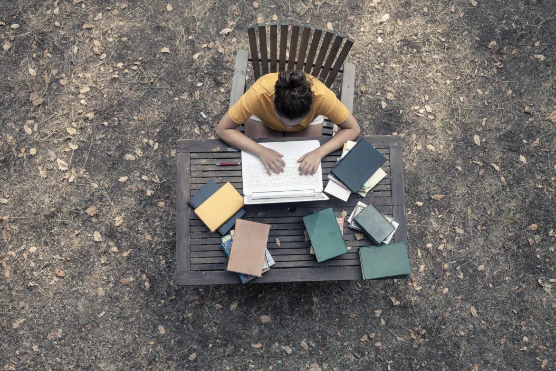 Ung dame som studerer utendørs ved et hagebord. Vi ser henne ovenfra, hun skriver på PC, og har mange bøker på bordet.